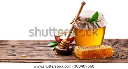 Glass can full of honey, apples  and on old wooden table. Clipping paths. - stock photo