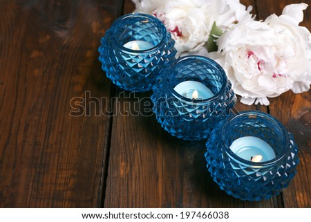 Glass candlesticks and flowers on color wooden background - stock photo