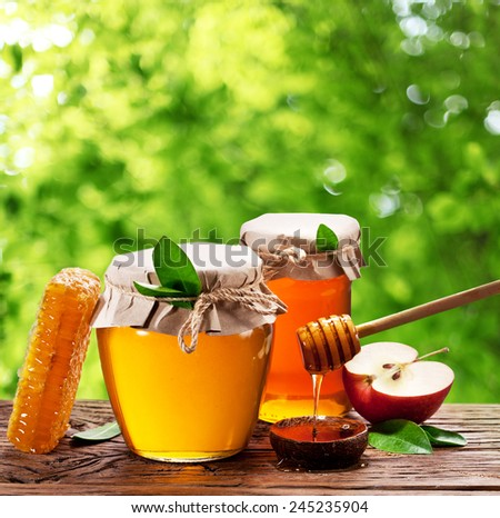 Glass cans full of honey, apples and combs on old wooden table in the garden. - stock photo