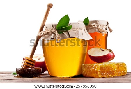 Glass cans full of honey, apples and honeycombs on wood. File contains clipping paths. - stock photo