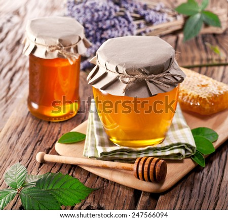 Glass cans full of honey on old wooden table. - stock photo
