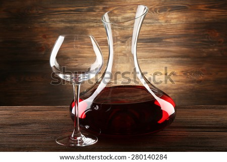 Glass carafe of wine on wooden background - stock photo