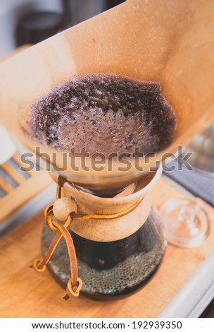 Glass Carafe with Ground Coffee Beans in Brown Paper Filter for Pour Over Style - stock photo