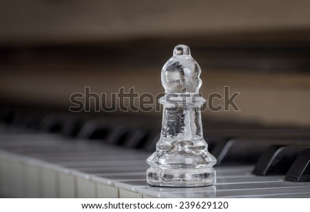 Glass chess bishop on the piano (shiny) - stock photo