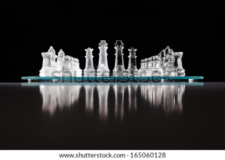 glass chess board with chess pieces on. - stock photo
