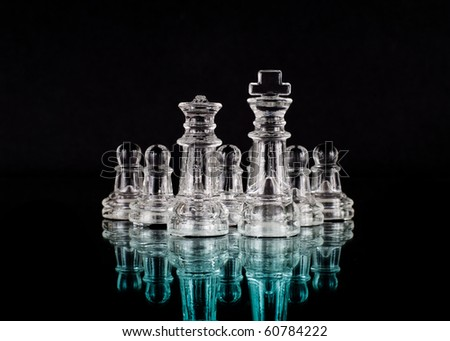 Glass Chess King and Queen and Their Pawn Army - stock photo