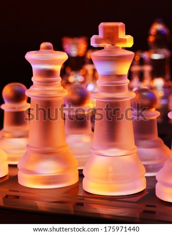 Glass chess on a chessboard lit by a colorful blue and orange light and placed on a glass chessboard - stock photo