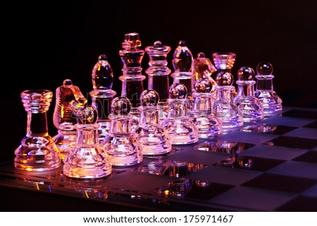 Glass chess on a chessboard lit by a colorful blue and orange light and placed on a glass chessboard