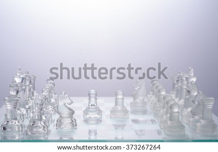 glass chess on the transparent chessboard - stock photo