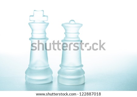 Glass chess pieces King and Queen are on a white background isolated. - stock photo