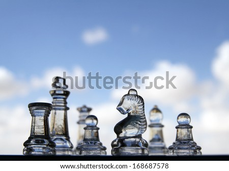 Glass chess pieces on the background of sky