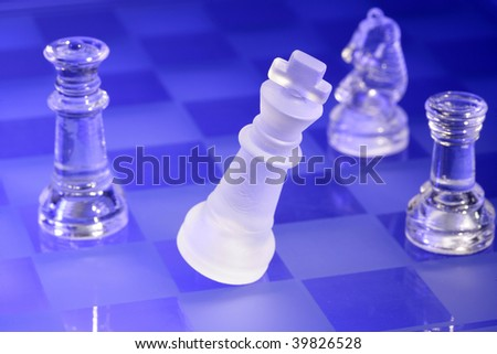 Glass chessmen in blue light, falling King