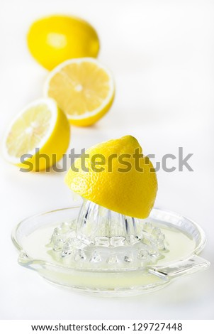 Glass citrus squeezer with lemons and juice on a white table