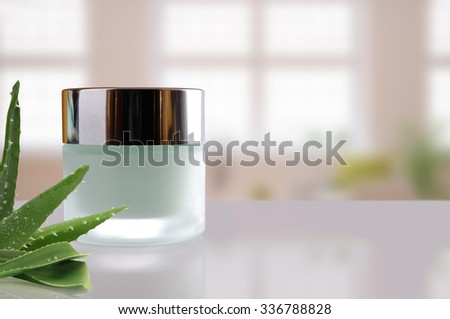 Glass closed jar with facial or body aloe vera cream on white table. Front view. Horizontal composition. Windows background. - stock photo