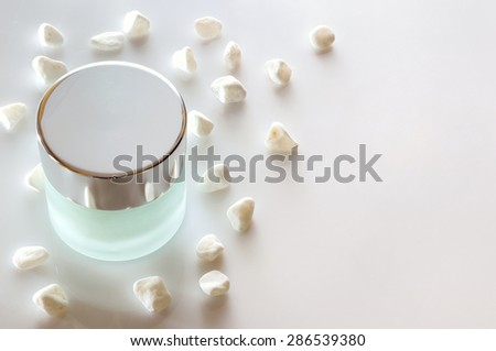 Glass closed jar with facial or body cream on white table with small white stones. Top view. White isolated. - stock photo