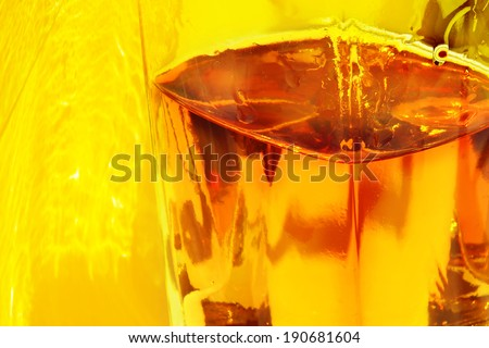 Glass cognac sunny yellow background. Close up