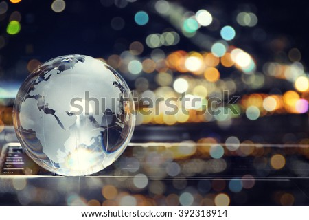Glass crystal globe on laptop keyboard  - stock photo