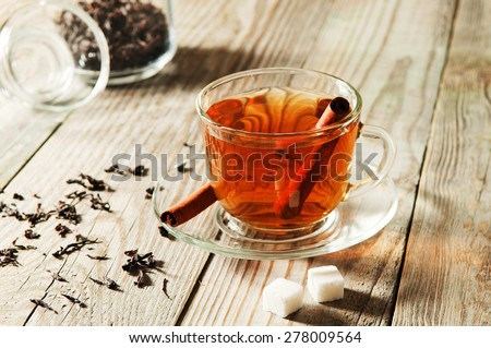 glass cup and saucer black tea with cinnamon standing on a wooden table. Next to a cup of black tea, two pieces are portioned sugar and scattered dry tea  - stock photo