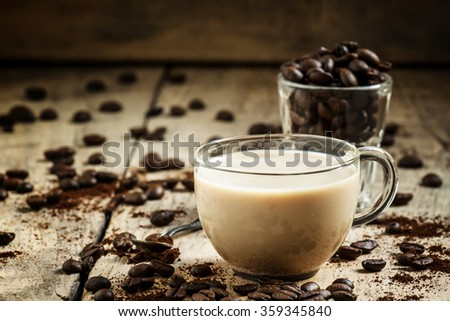 Glass cup of coffee with milk, spilled grain and ground coffee on the old wooden background in rustic style, selective focus