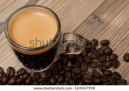 Glass Cup of Espresso on Wooden Table With Coffee Beans - Shallow Depth of Field - stock photo