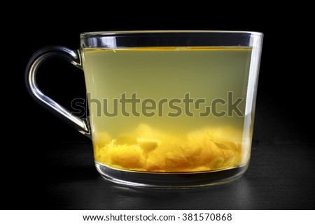 Glass cup of fresh tropical orange and citrus fruit tea isolated on black. Fruit pieces visible.
