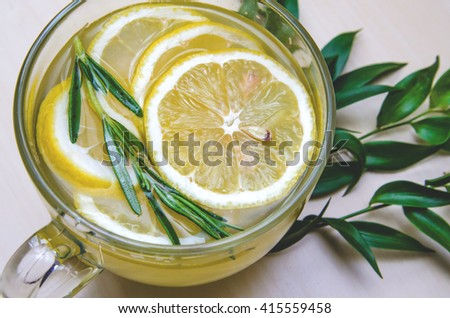 Glass cup of ginger tea with yellow lemon served round frame green leaves ruscus flowers on a light wooden rustic wall background. Still life, food and drink, healthcare concept, top view. Eco style. - stock photo