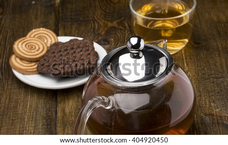 Glass cup of green tea and teapot with various cookies on wooden background - stock photo