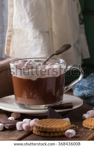 Glass cup of Hot chocolate with marshmallows and cookies, chopping chocolate and mittens over wooden window sill near window in sunny day. Rustic style.