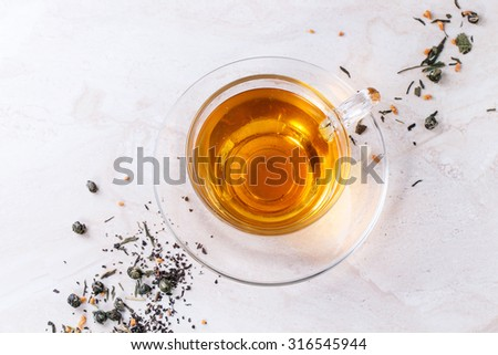 Glass cup of hot tea on saucer with dry green and black tea leaves over white marble backgtound. Top view - stock photo