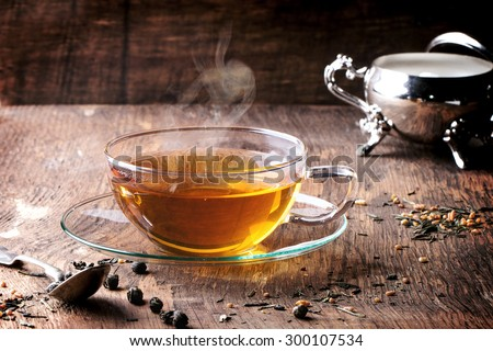 Glass cup of hot tea with dry green tea leaves, vintage spoon and sugar. Rustic wooden backgtound. - stock photo