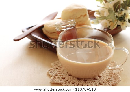 glass cup of milk tea with scone on background - stock photo
