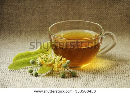 Glass cup of tea. Linden flowers. Still on sackcloth. - stock photo