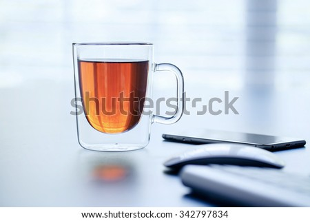 Glass cup of tea on a table in the office.