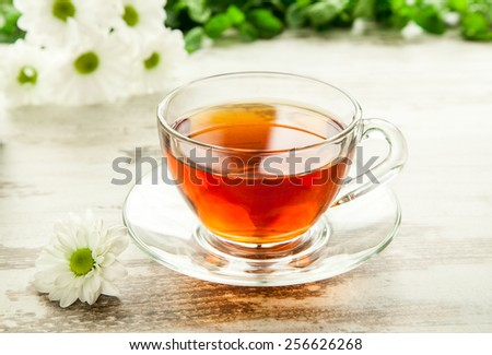 Glass cup of tea on a wooden table and a flower. - stock photo