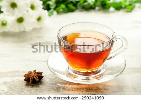 Glass cup of tea on a wooden table with flowers, mint leaves and star anise. - stock photo