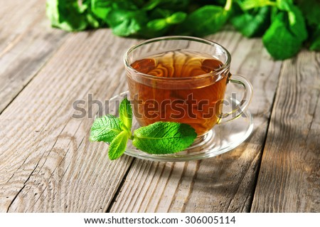 glass cup of tea with a mint leaf on a saucer on a wooden table closeup. Copy space. Free space for text - stock photo