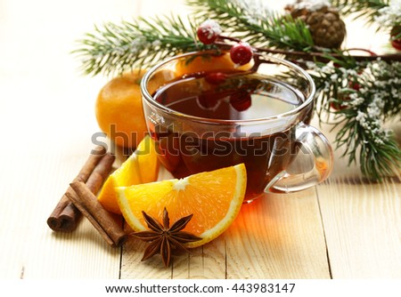 glass cup of tea with anise, cinnamon and citrus fruits winter drink, Christmas decorations