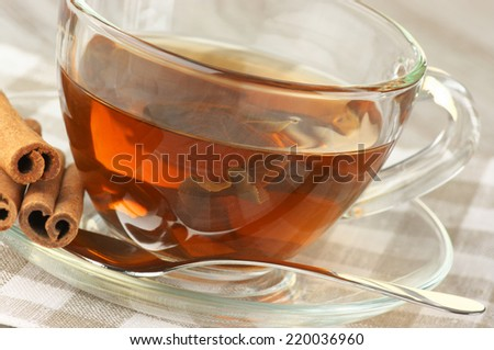 Glass cup of tea with cinnamon close-up on napkin.