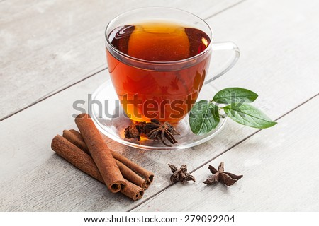Glass cup of tea with cinnamon on rustic table. - stock photo
