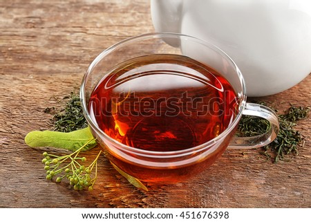 Glass cup of tea with fresh linden and white teapot on wooden background