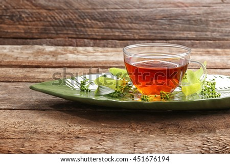 Glass cup of tea with fresh linden in green plate on wooden background - stock photo