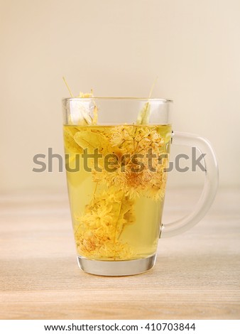 Glass cup of tea with lime dry blossom. Linden decoction. - stock photo