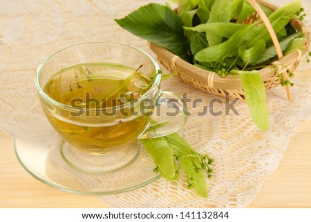 Glass cup of tea with linden on wooden table close-up