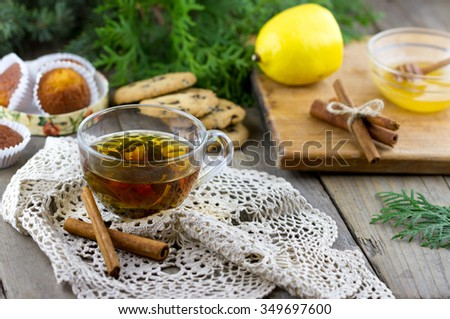 Glass cup of tea with mint. Homemade chocolate chip cookies, lemon, cinnamon sticks, gift box and thuja branches on wooden background - stock photo