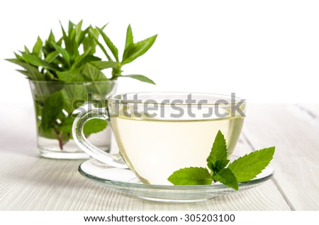 Glass cup of tea with mint on the white wooden table - stock photo