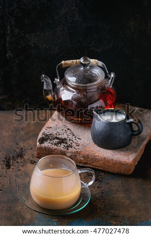 Glass cup on saucer of black tea with milk, teapot with hot black tea, standing on clay board with jug of milk over old wooden background. With copy space