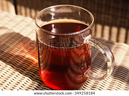 Glass cup with black tea
