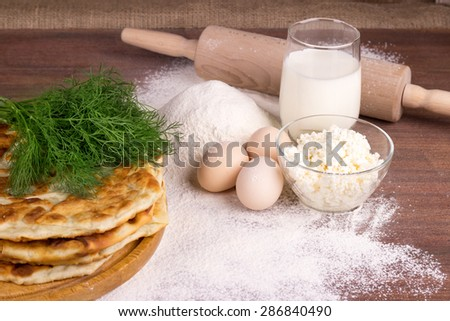 glass cup with milk, a glass bowl with cottage cheese, eggs, flour, dill, Moldovan palanitsa on a wooden table
