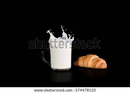 Glass cup with milk and croissant on a dark background, spray milk rise up