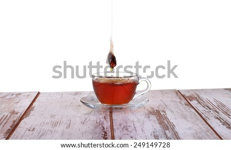 Glass cup with tea and a lemon on a glass saucer isolated on white background - stock photo